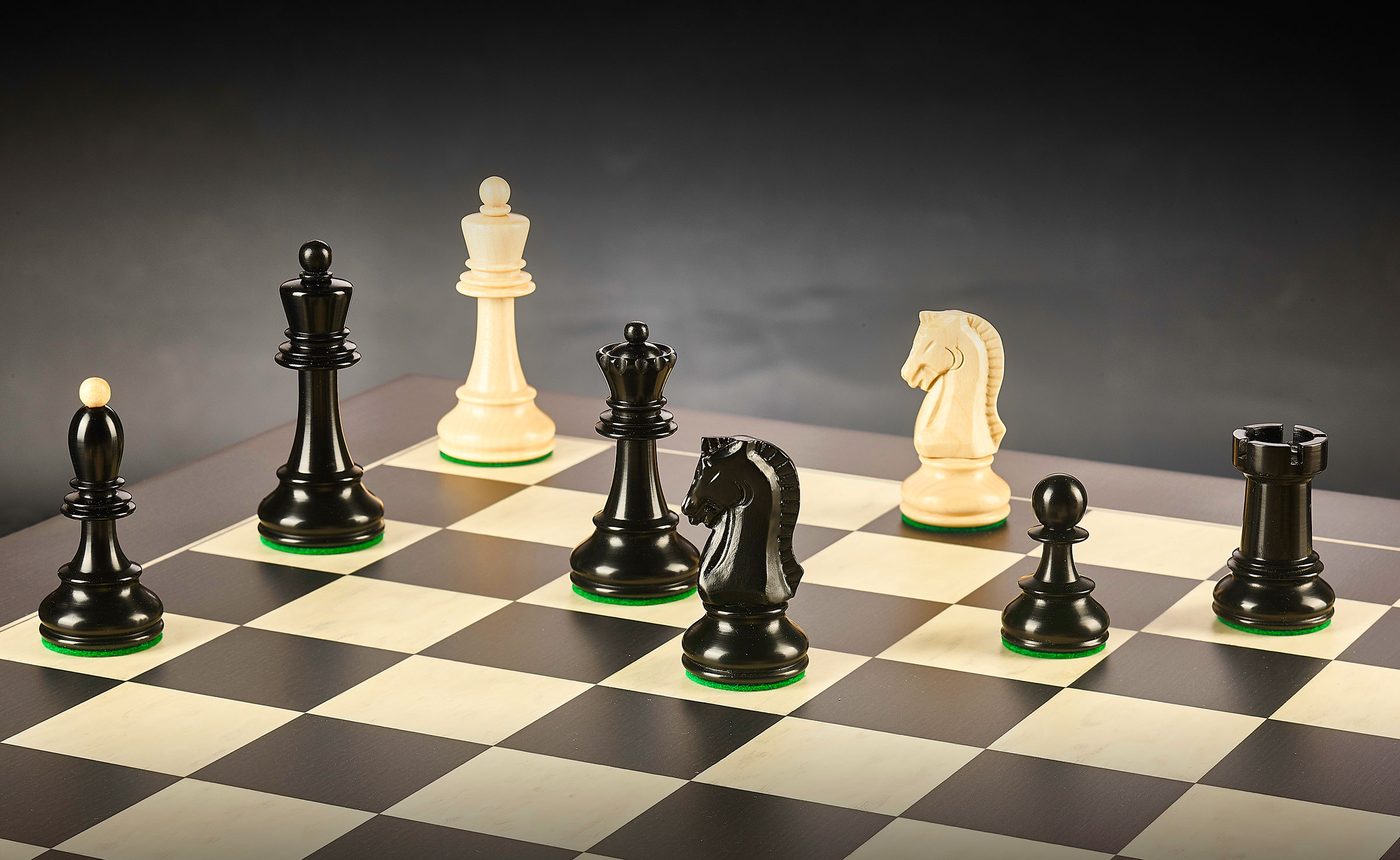 maple and black chess pieces on board